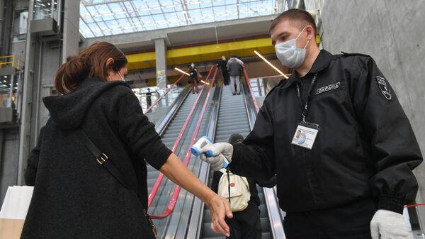 Сотрудник ТЦ измеряет температуру у посетителя