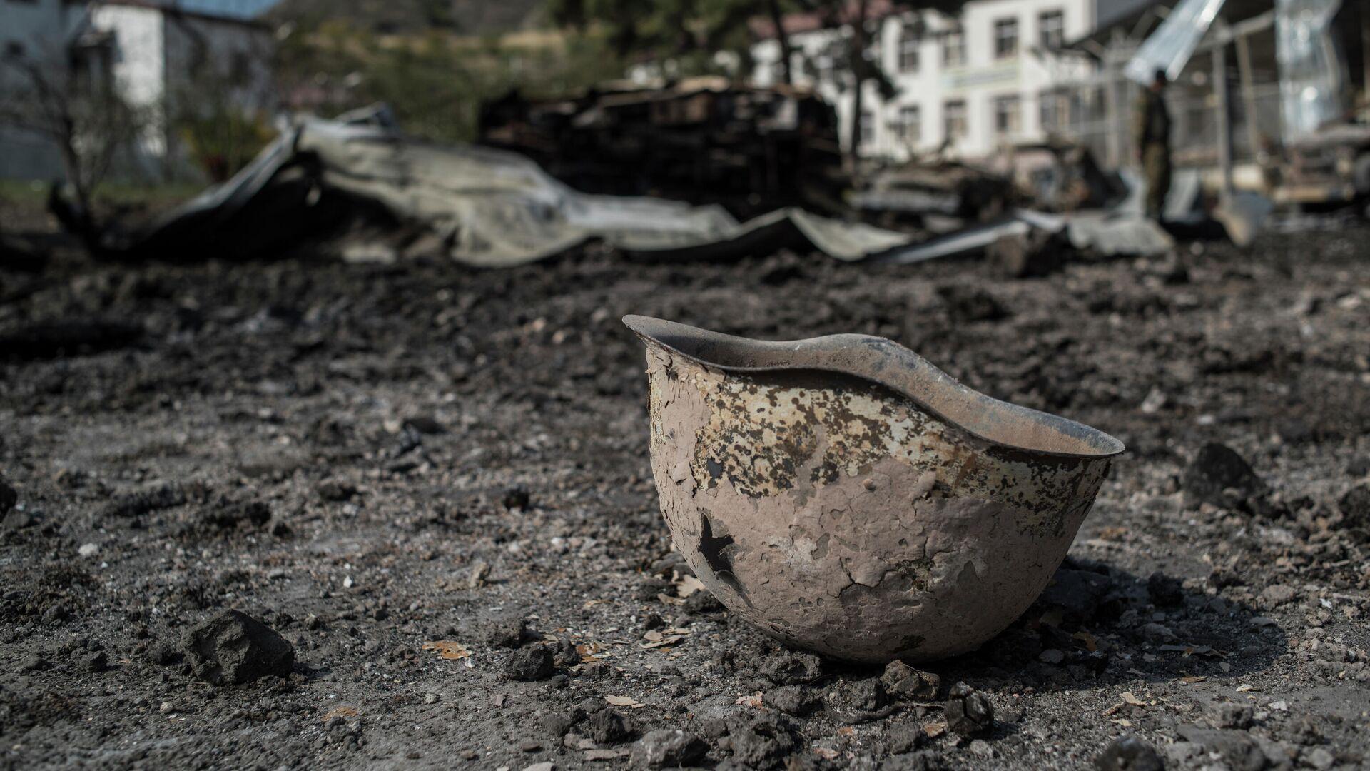 Пробитая каска на территории у госпиталя в Мартакерте, разрушенного в результате обстрела - РИА Новости, 1920, 19.10.2020