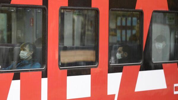 Пассажиры в медицинских масках в вагоне электрички