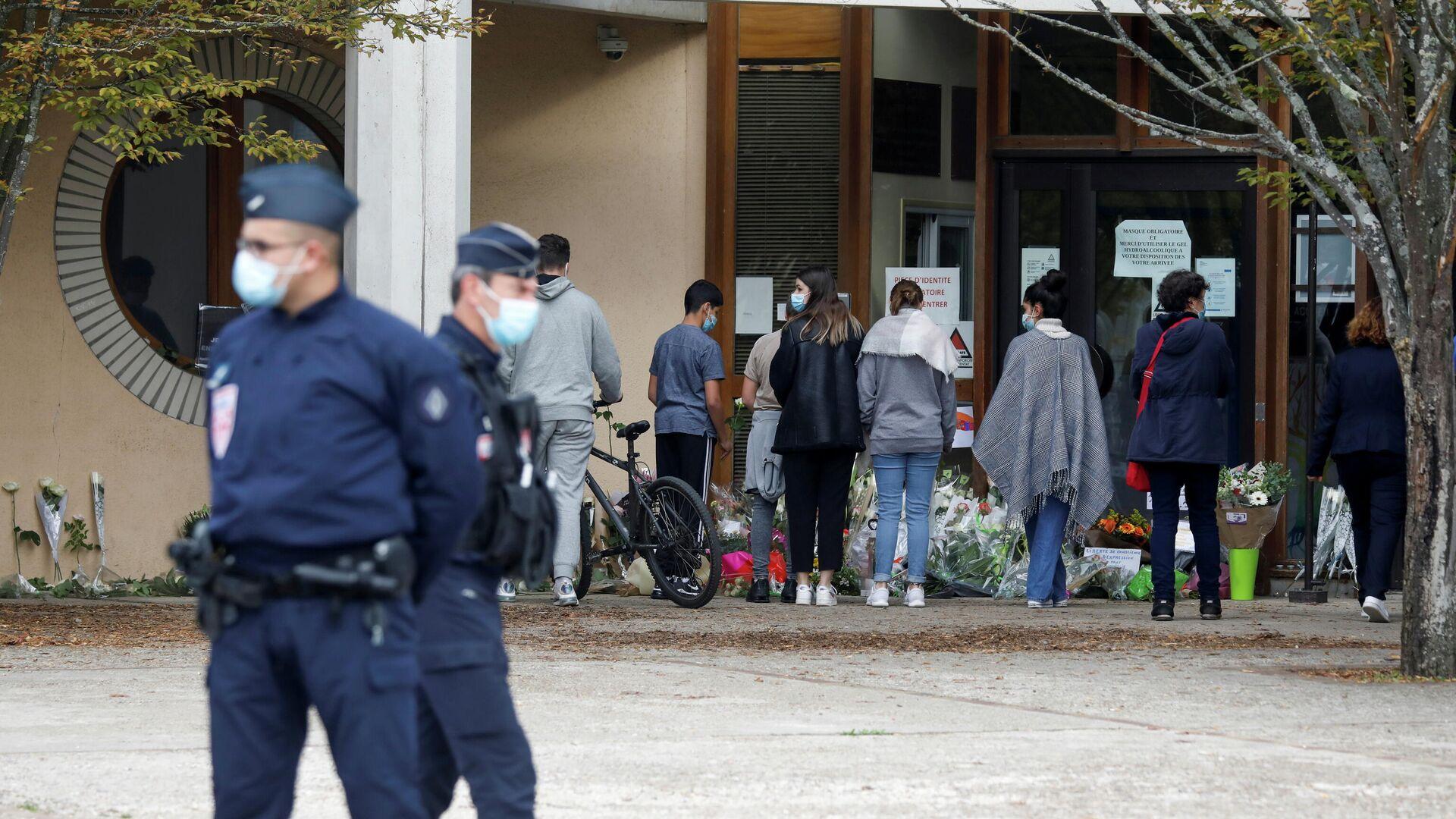 Люди несут цветы к месту, где было совершено нападение на учителя в коммуне Конфлан-Сент-Онорин, Франция - РИА Новости, 1920, 18.10.2020