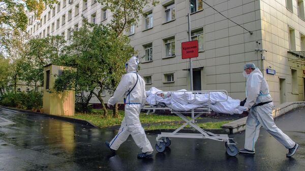 Медицинские работники оказывают помощь пациенту с COVID-19 в городской клинической больнице № 52