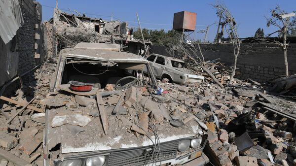 Машина под обломками разрушенного после обстрела дома в Гяндже