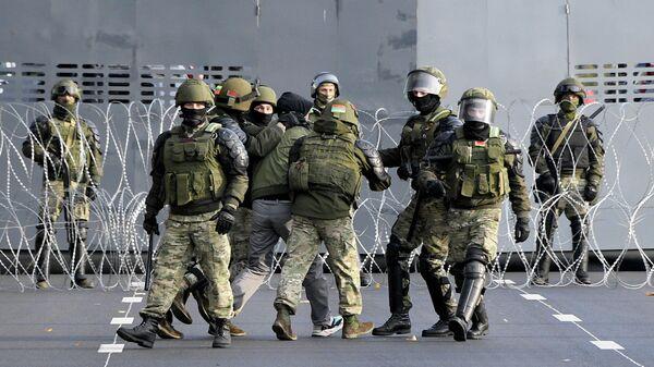 Сотрудники правоохранительных органов Белоруссии задерживают участника несанкционированной акции протеста Партизанский марш на улице в Минске