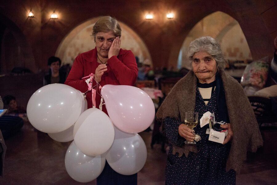 Жители Степанакерта скрываются от обстрелов города в нижней части храма. Женщина справа отмечает день своего рождения