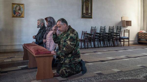 Люди молятся в храме в Степанакерте
