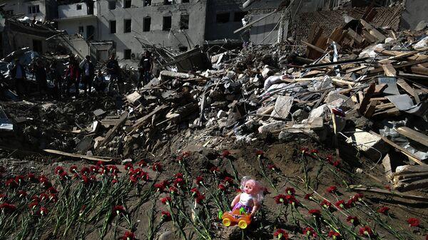 Цветы на месте гибели людей в результате обстрела города Гянджа