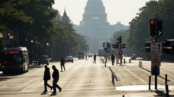 Прохожие переходят улицу перед зданием Капитолия в США