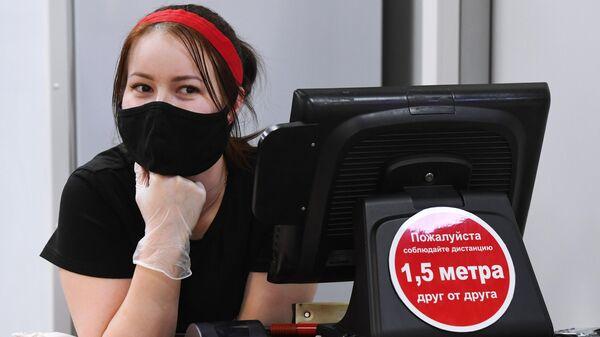 Продавец в защитной маске в одном из продовольственных магазинов
