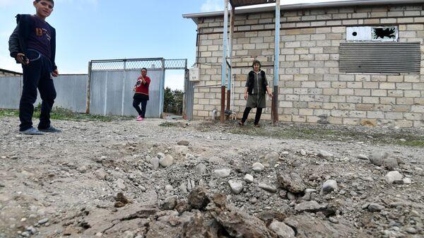 Жители поселка Сафарли в Агдамском районе Азербайджана у поврежденного после обстрела дома