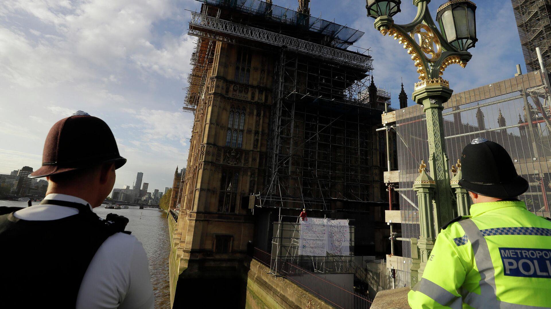Сотрудники полиции наблюдают за протестующим в костюме человека-паука на здании Биг-Бена в Лондоне - РИА Новости, 1920, 08.02.2021