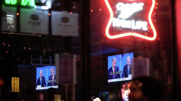 Экран с трансляцией финального раунда дебатов с участием президента США Дональда Трампа и его соперника - кандидата в президенты США от Демократической партии Джо Байдена в одном из баров Нью-Йорка