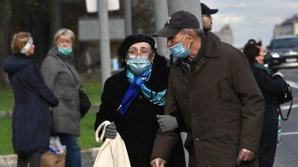 Пассажиры в защитных масках на остановке Ленинский проспект в Москве