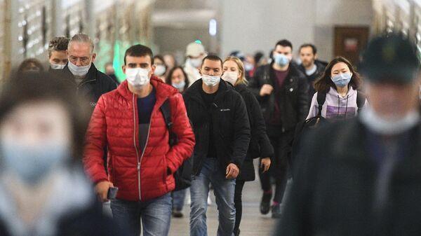 Пассажиры в защитных масках на одной из станций Московского метрополитена