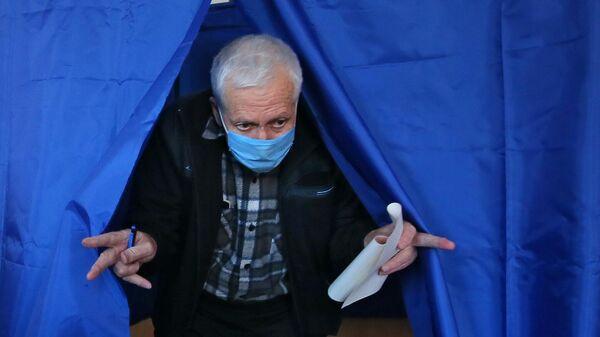 Мужчина голосует на одном из избирательных участков в Киеве