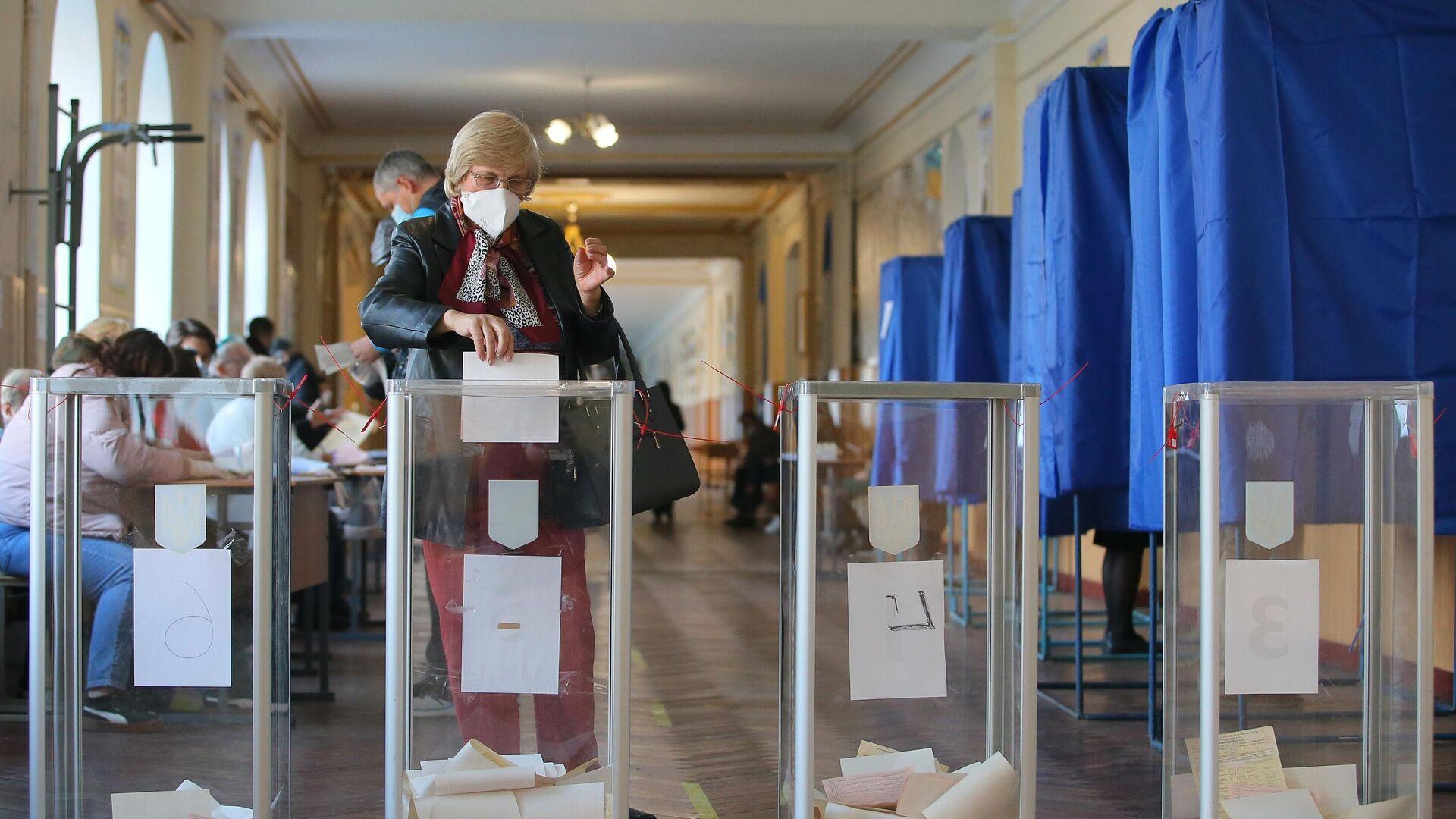 Женщина голосует на одном из избирательных участков в Киеве - РИА Новости, 1920, 26.10.2020