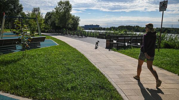 Девушка гуляет с собакой около набережной Москвы-реки в Капотне