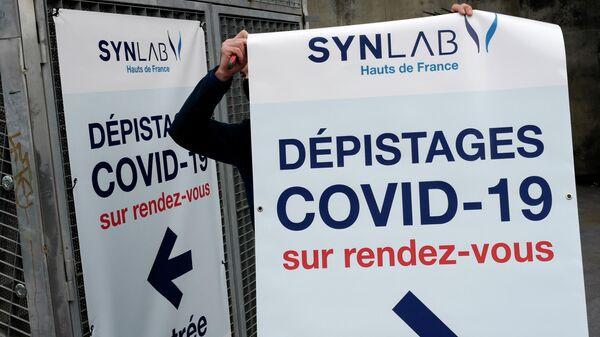 Мужчина вешает плакат с информацией о тестировании на COVID-19 на арене Lille Zenith Arena в Лилле, Франция