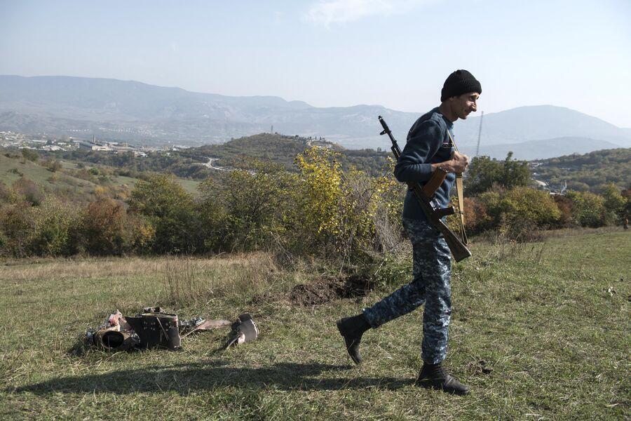 Мужчина с автоматом возле сбитого беспилотника в Степанакерте