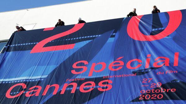 Рабочие во время установки баннер на фасаде дворца фестивалей в Каннах