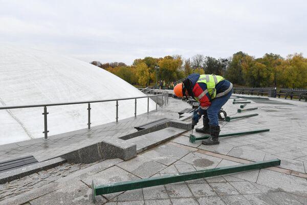 Рабочий устанавливает ограждение вокруг фонтана после демонтажа в парке Царицыно в Москве