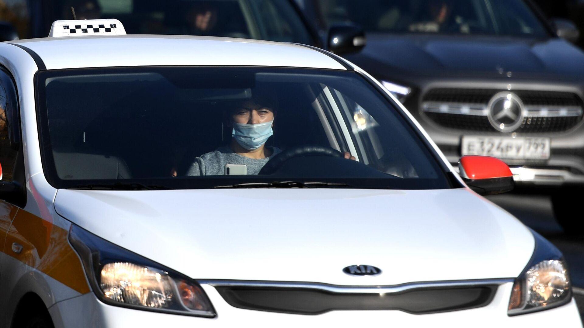 Водитель в защитной маске за рулем такси на одной из улиц в Москве - РИА Новости, 1920, 08.02.2021
