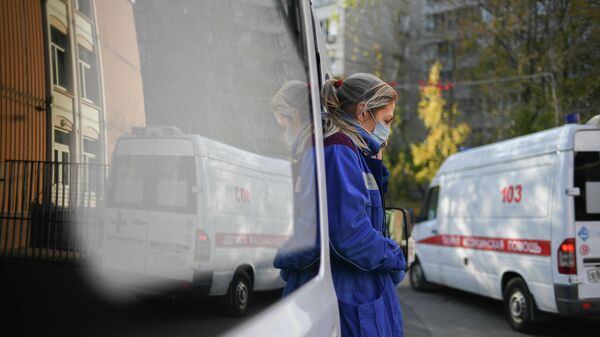 Медицинский работник у машины скорой помощи в Москве