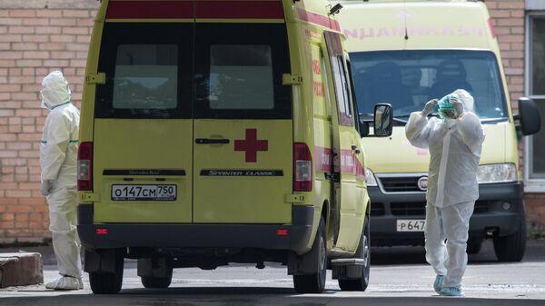 Медицинские работники и автомобили скорой помощи на территории больницы
