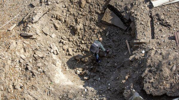 Журналист в воронке от снаряда в городе Шуша