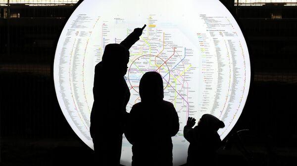 Пассажиры осматривают схему Московского метрополитена на станции МЦД Долгопрудная