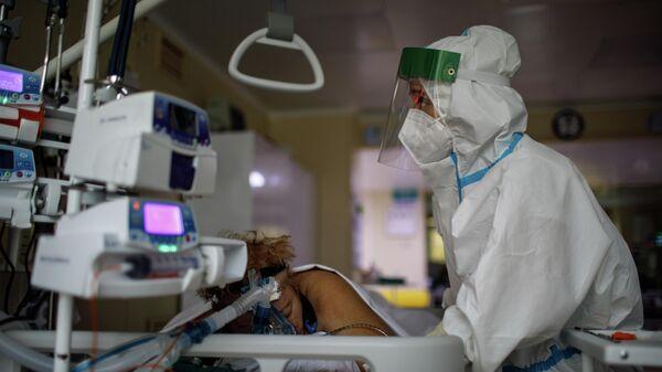 Медицинский работник оказывает помощь пациенту с COVID-19 в отделении реанимации и интенсивной терапии городской клинической больницы № 52