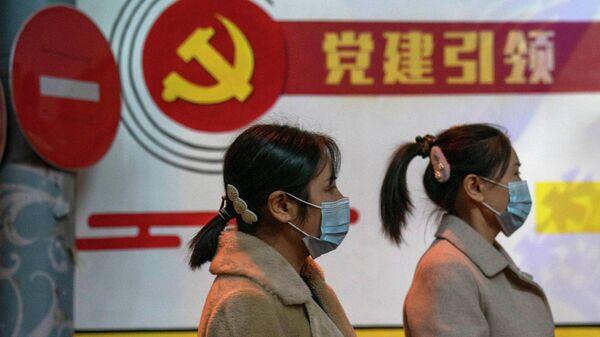Девушки на фоне плаката Коммунистической партии Китая
