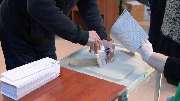 Мужчина принимает участие в голосовании на парламентских выборах в Грузии на одном из избирательных участков в Тбилиси