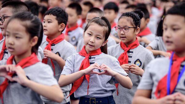 Учащиеся начальной школы во время церемонии поднятия флага в первый день нового семестра в Шэньяне, провинции Ляонин
