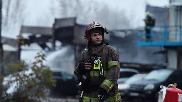 Сотрудник МЧС РФ на месте возгорания складского помещения на улице Газопровод в Москве