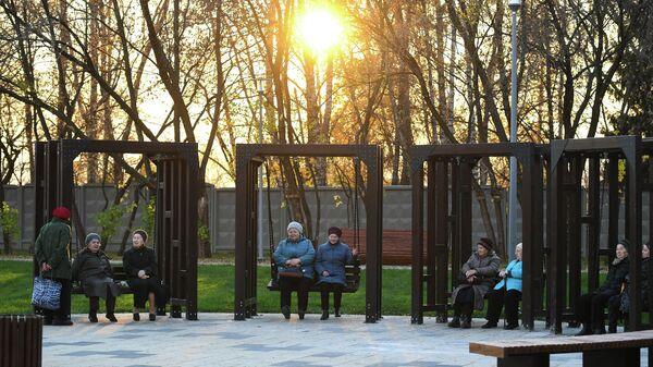 Пенсионеры сидят на качелях в Капотне