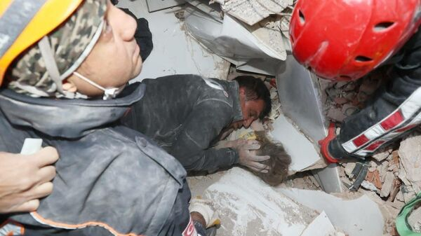 Турецкие спасатели достают из-под завалов разрушенного здания в Измире выжившую девочку