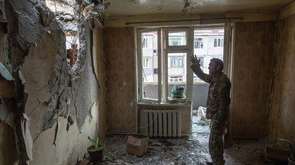 Мужчина в разрушенной квартире в Степанакерте