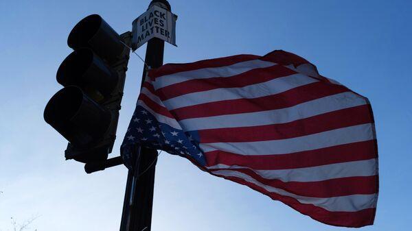Флаг Соединенных Штатов Америки на светофоре на одной из улиц в Вашингтоне в преддверии выборов президента США