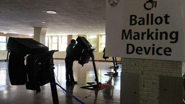 Избиратель опускает бюллетень в урну для голосования на одном из избирательных участков в Вашингтоне