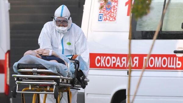 Работник скорой помощи и пациент у больницы в Коммунарке