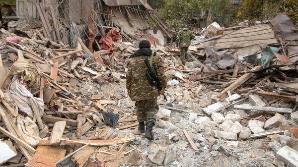 Вооруженные люди возле дома, поврежденного в результате обстрела Степанакерта