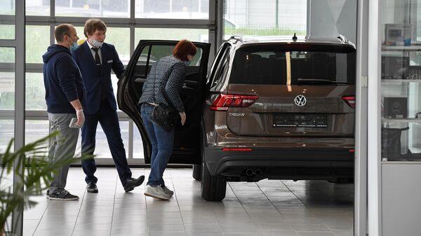 Посетители автосалона в Москве осматривают автомобиль