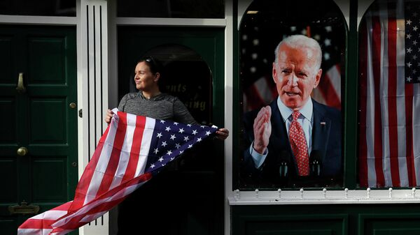 Сторонница Джо Байдена с флагом США на улице города Баллина, Ирландия