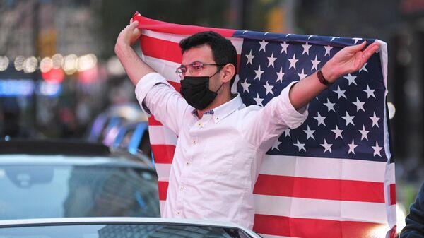 Молодой человек на Таймс-сквер в Нью-Йорке после новостей о победе на выборах президента США кандидата от Демократической партии Джозефа Байдена