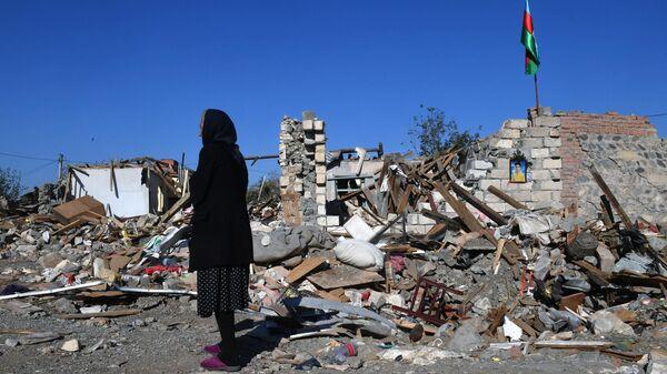 Женщина у разрушенного дома в городе Гянджа