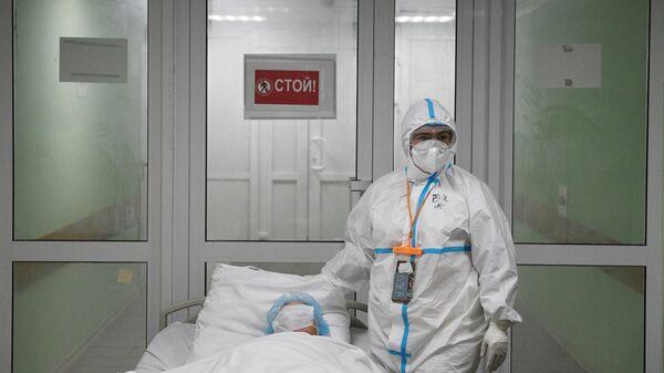Медицинский работник и пациент в ковид-госпитале, организованном в городской клинической больнице №15 имени О. М. Филатова в Москве