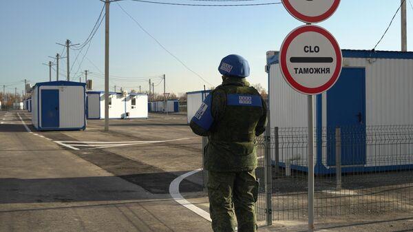 Сотрудник СЦКК на контрольном пункте въезда-выезда Луганск - Счастье у линии соприкосновения в Донбассе