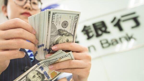 Банковский служащий пересчитывает доллары в Наньтуне, Китай