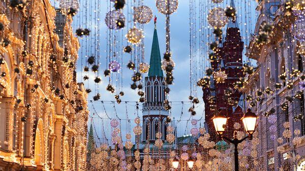 Вид на Никольскую башню Московского Кремля сквозь гирлянды на Никольской улице