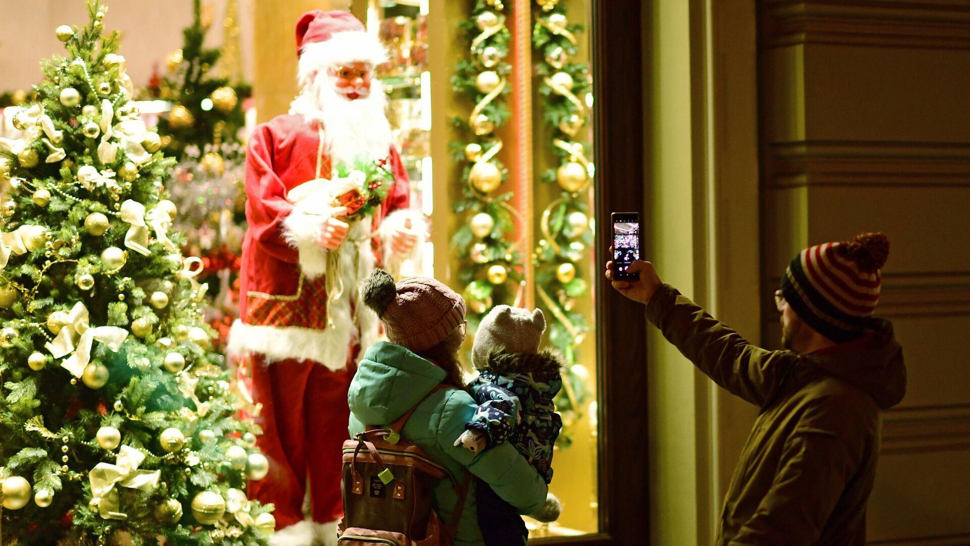 Прохожие фотографируют Санта Клауса в витрине на Никольской улице в Москве - РИА Новости, 1920, 12.11.2020
